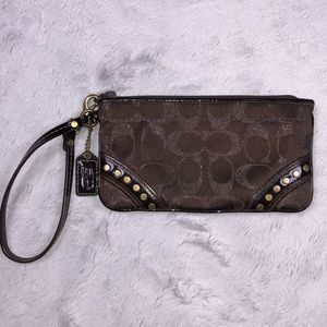 """Coach """"C"""" shimmer patent wristlet with studs."""